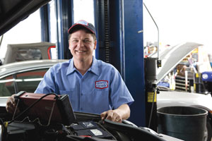 Image of Smiling AAMCO Mechanic giving an Engine a Tuneup