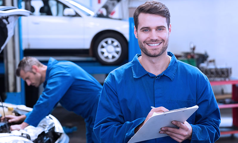 image of mechanic smiling with clipboard